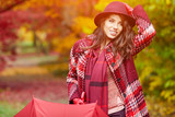 Young woman with red umbrella walking on autumn city park. Beautiful fall time in nature - 168338108