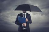 businessman below storm with umbrella - 168349789