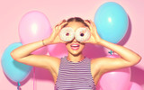 Joyful model beauty girl holding donuts and colorful air balloons over pink background - 168382369