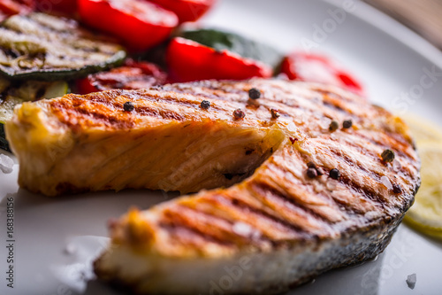 Papiers peints Steakhouse Salmon. Grilled salmon steak with tomatoes and zucchini on white plate