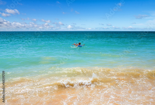 jeune femme sur un matelas gonflable dans le lagon Poster
