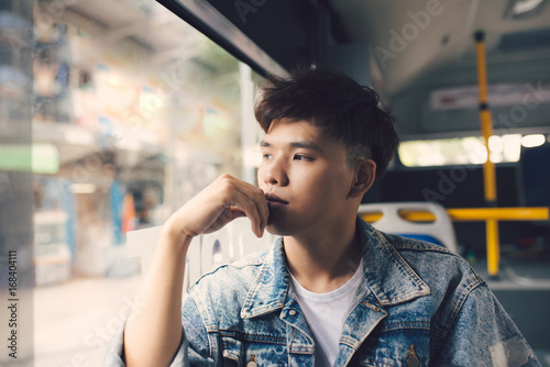 Asian man sitting in city bus looking through window. Poster