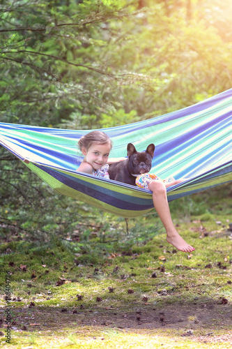 girl is playing on a hammock with French bulldog