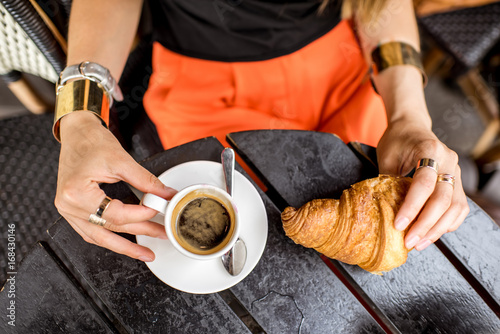 Top view on the coffee and croissant on the black table. Traditional french breakfast