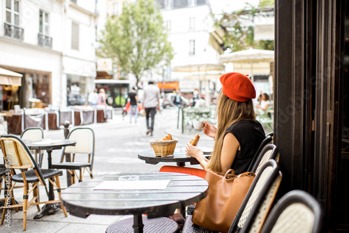 Young stylish woman in red beret having a french breakfast with coffee and croissant sitting oudoors at the cafe terrace - 168430150