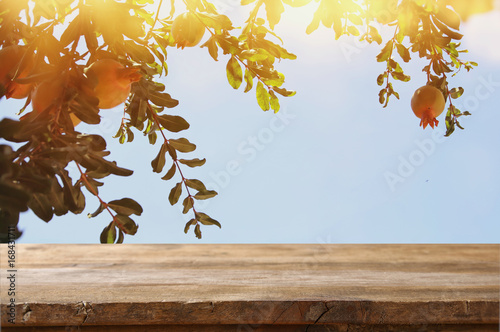 vintage wooden board table in front of dreamy pomegranate tree landscape - 168431711