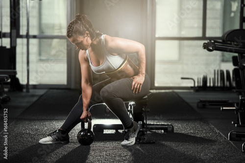 Sticker Strong brunette athletic woman sitting on a bench wearing a sports bra and black tights about to work out this a kettlebell in a dark gym with a light flair behind