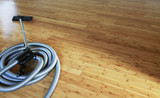Fototapety Beautiful bamboo hardwood floor with a central vacuum cleaner. Cleaning contest.
