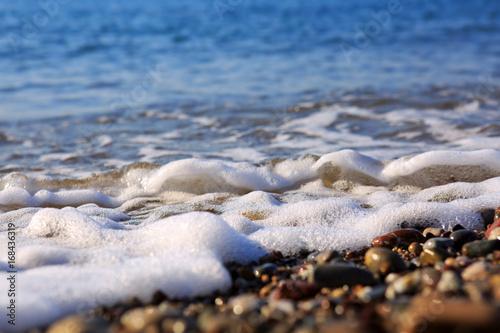 Waves washing over gravel beach, macro shot. Poster