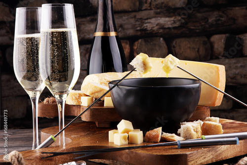 Gourmet Swiss fondue dinner on a winter evening with assorted cheeses on a board Poster