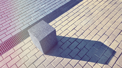 Vintage toned picture of a concrete block on pavement, abstract urban background.
