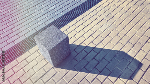 Vintage toned picture of a concrete block on pavement, abstract urban background.  - 168452548