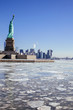 Statue of Liberty / Ellis Island surrounded by a frozen Hudson River; Downtown Manhattan skyline in background