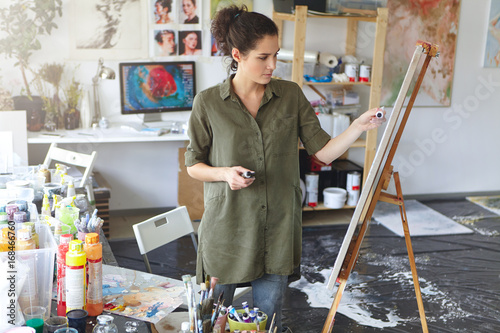 Candid shot of beautiful young dark-haired woman of creative occupation standing in modern workshop interior with painting accessories, working on painting, looking serious and busy, choosing color