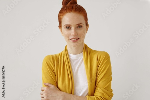 Close up portrait of lovely tender young Caucasian woman with freckles on her pretty face and ginger hair bun standing against blank copyspace studio wall, dressed casually, keeping arms folded