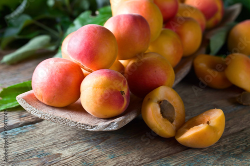 Juicy fresh apricots with leaves on old wooden table .
