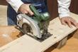 Pracownik budowlany przecina deskę ręczną tarczową piłą elektryczną.