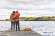 Couple on the dock with a dog, looking at view