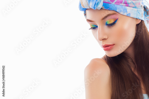 Fashion portrait of a beautiful young woman in headscarf. Colored makeup