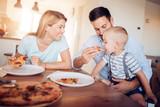 Happy lovely family eating pizza - 168499971
