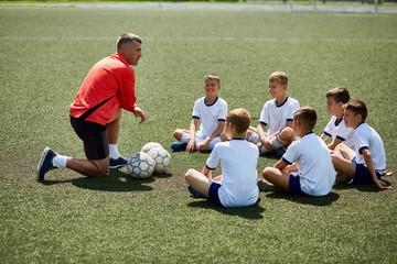 Coach Instructing Junior Football Team