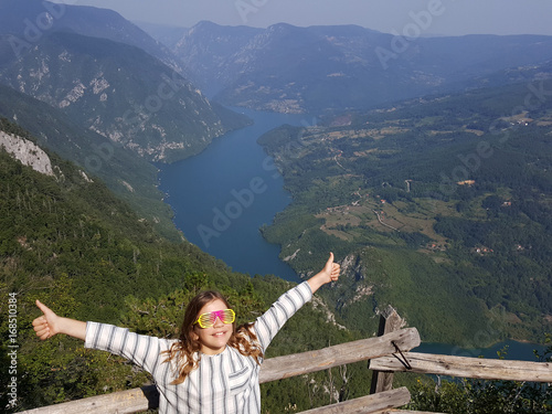 Poster happy little girl with colorful sunglasses and thumbs up on mountain
