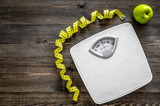 Lose weight concept. Bathroom scale, measuring tape, apples on wooden background top view copyspace - 168519351