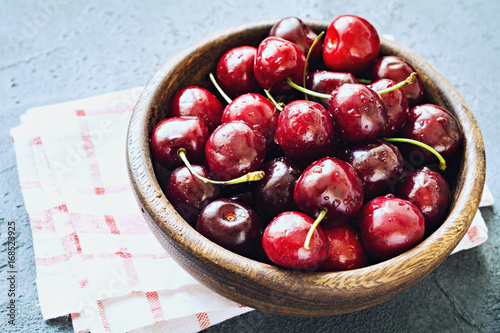 Closeup view of sweet cherries in wooden bowl on napkin over blue concrete background. Selective focus