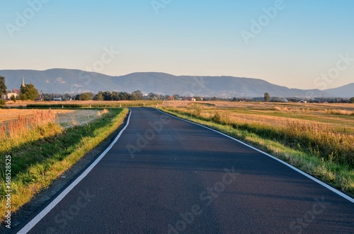 Fotobehang Zomer Summer rural landscape. Asphalt road with mountains and village in the background.