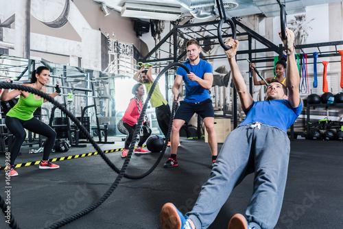 Sticker Männer und Frauen beim Crossfit Training im Fitnessstudio treiben Sport an Ringen und Seil