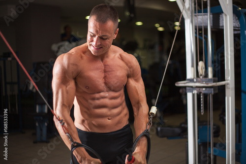 Wall mural bodybuilder works out pushing up excercise in gym