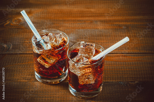 Beautiful cold drink of Cola with ice cubes with a boiler straws in glasses on w Poster