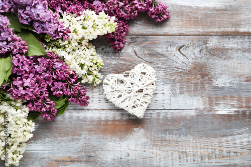 Branch of lilac flowers with heart on wooden table