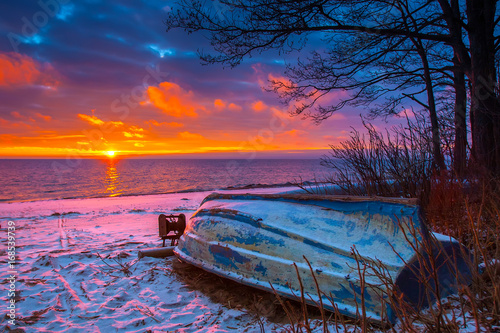 Poster Crimson Boat on the beach. Wooden boat at sunset.