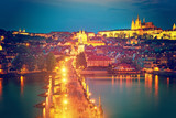 View of Charles Bridge, Prague Castle and Vltava river in Prague, Czech Republic during blue hour. The world famous Prague and Europe landmark.