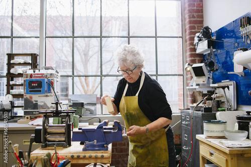 Art Jeweler Working in Studio © Laura