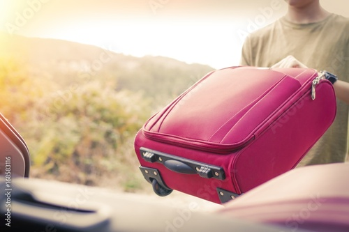 putting the suitcase in the car, luggage and travel