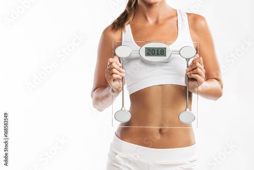 Zamknij się z brzucha kobiety, trzymając skalę wagi z roku 2018 napisane na nim - Nowy rok zważyć t straty rozdzielczości