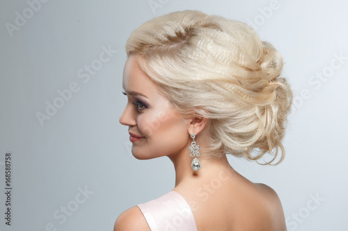 A smart wedding hairstyle on a blonde woman on a gray background. © ksi