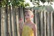 Little girl is eating Saskatoon berries near wooden fence - summer Russian village