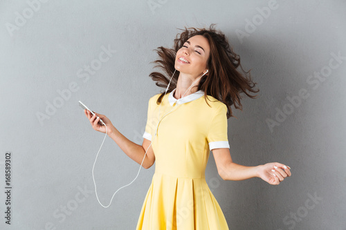 Happy relaxed girl enjoy listening to music with earphones