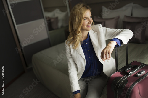 Portrait of attractive businesswoman sitting on bed