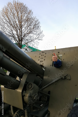 The boy is playing on a large heavy cannon from the times of World War II on the Poster