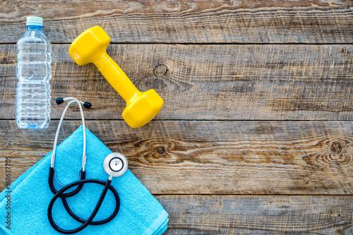 Sport i zdrowie. Zdatność. Dumbbells i stetoskop na drewnianym tło odgórnego widoku copyspace