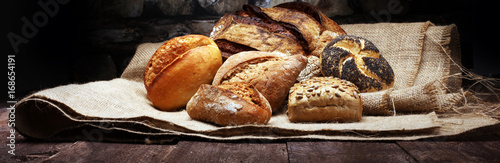 canvas print picture Different kinds of bread and bread rolls on wooden table
