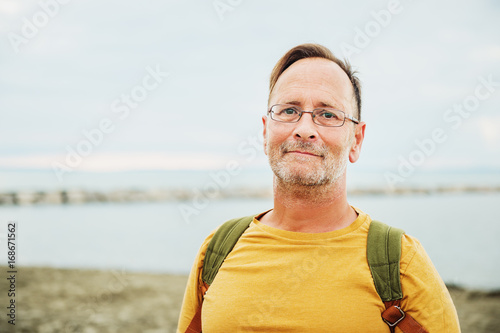 Poster Handsome man on summer vacation by the sea, wearing yellow safran t-shirt and ba