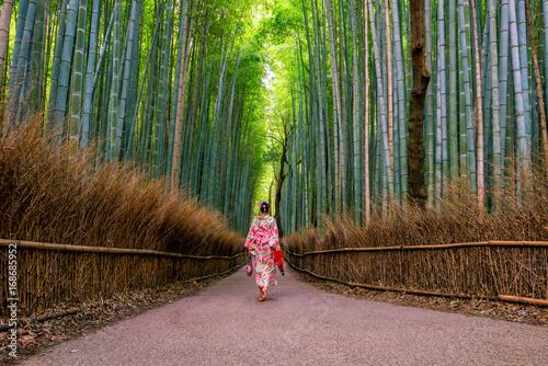 Woman in traditional Yukata with red umbrella at bamboo forest of Arashiyama © f11photo