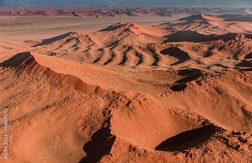 Foto op Canvas Baksteen Namib desert, Sossusvlei. Aerial panorama of the biggest red dunes in Sossusvlei area taken from the helicopter. Annual growth of the area of sand. Global warming on the planet.