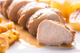 Filetto di maiale arrosto con patate e spicchi di mela arrostite servite su un piatto - 168706783