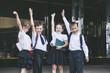 Beautiful school children active and happy on the background of school in uniform